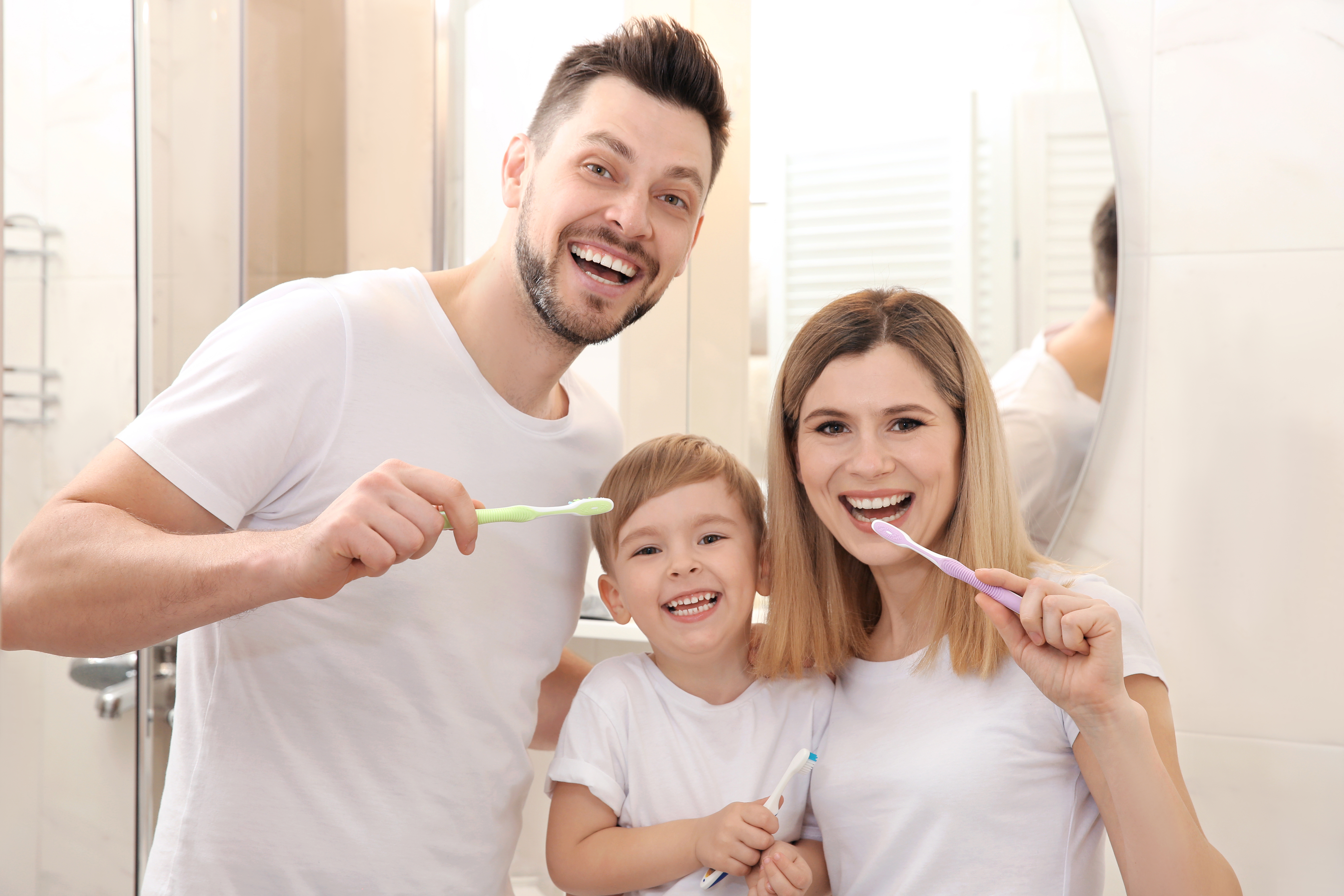 family holding tooth brushes